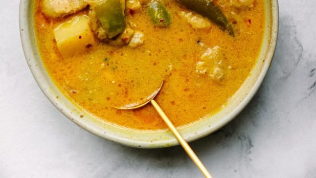 A bowl of Coconut Chicken Curry with Potatoes with a golden spoon.
