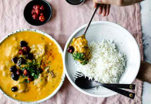 Using a spoon to scoop Kadhi Pakora on to a plate with basmati rice and a black spoon and fork