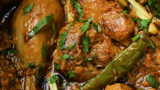 Closeup of Achari Chicken garnished with green chili and julienned ginger