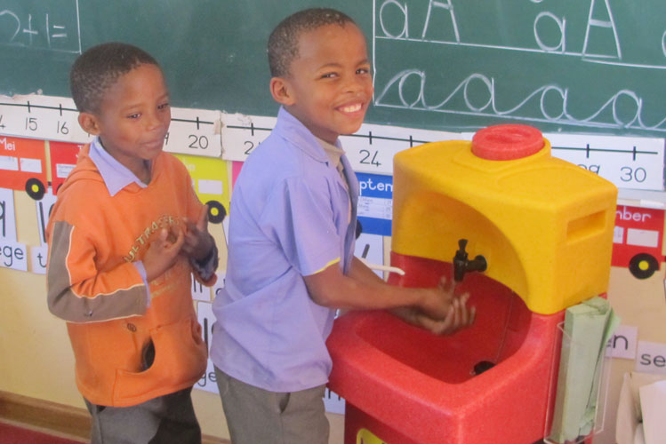 Young children washing hands in Nigeria with portable sink