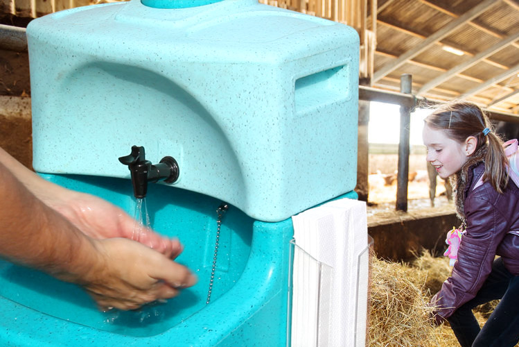 Washing hands with portable sinks on farm visit