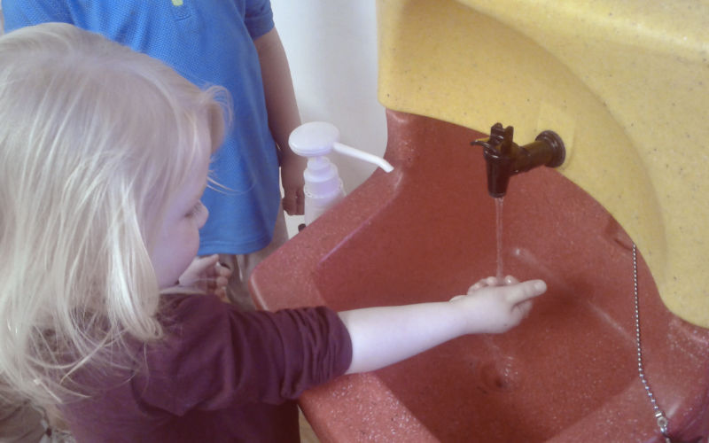 A preschool child being taught to wash her hands with a KiddiSynk