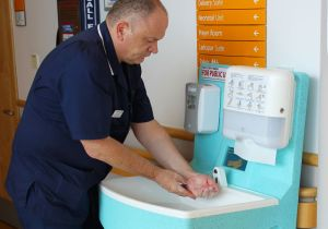 Medical staff member washing hands with a portable handwash station
