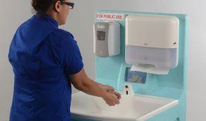 A nurse displays effective hand hygien techniques using a portable wash station