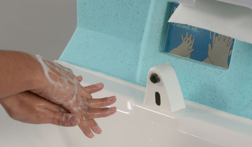 A nurse washing hands with portable handwash station with instructional video screen
