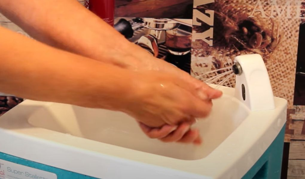 Caterer washing hands with a portable sink