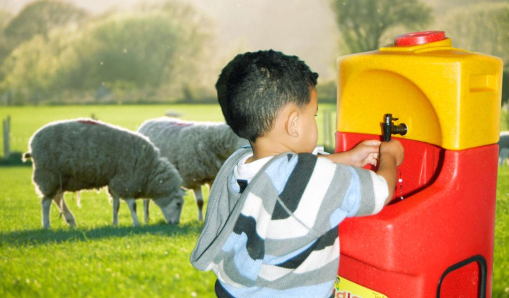 Child washing hands with a portable sink on farm open day