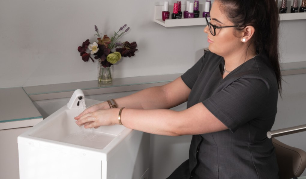 Beautician washing hands with a Teal HandSpa relocatable unit