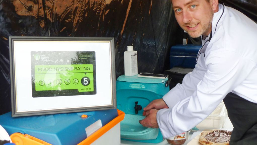 A street food caterer washing hands with a Teal Handeman Xtra portable handwash unit