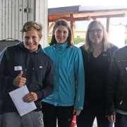 Siegerteam lächelt und hält Urkunde in der Hand.