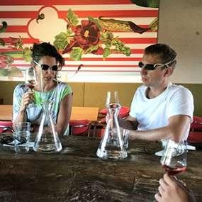 Frau und Mann kosten einen Wein und versuchen den Geschmack als Teambuilding Aufgabe blind zu erraten und finden gemeinsam eine Antwort
