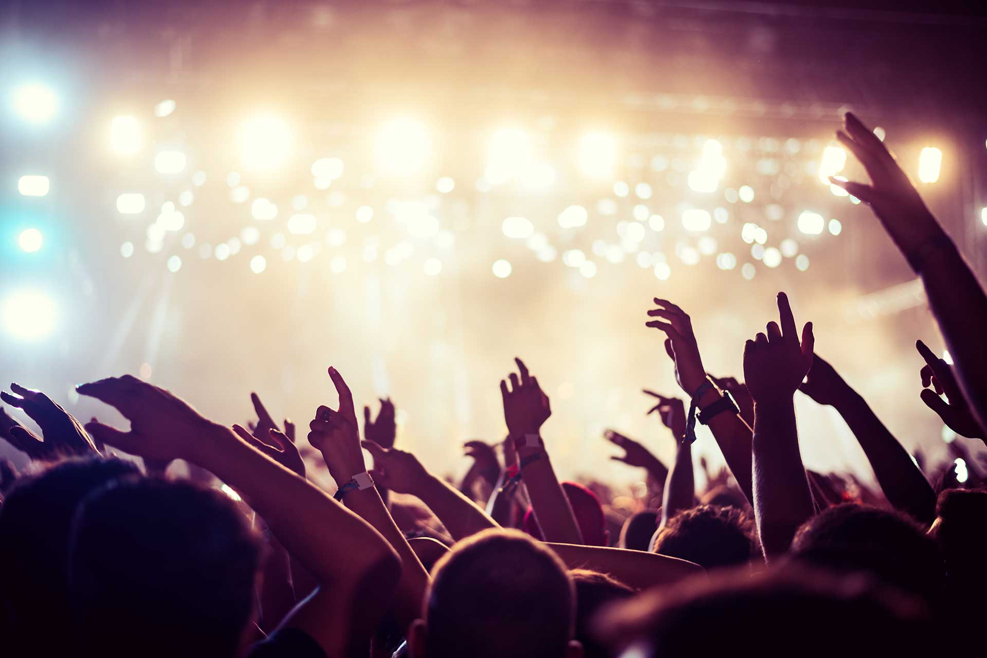 People at a concert waving their hands in the air