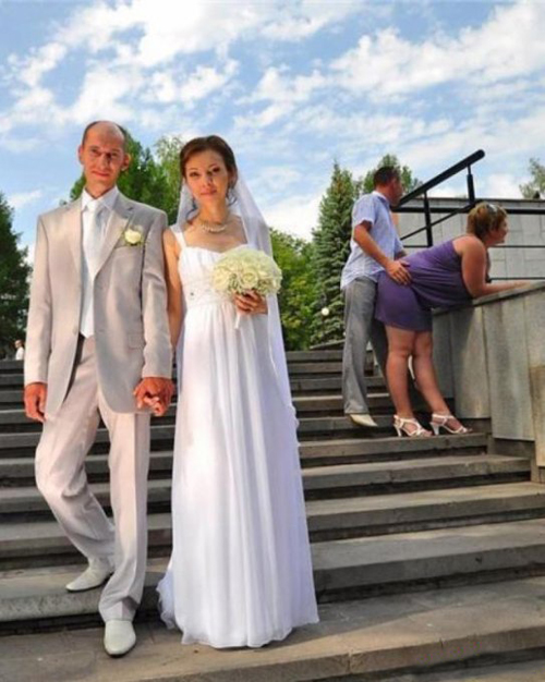 Wedding picture on stairs with couple humping in the background, funny wedding pictures, bad wedding, wedding photography worst wedding wedding disasters, strange weird, wedding fail,