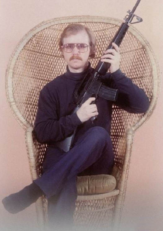 Man With Assault Rifle in Wicker Chair Bad Family Photos Worst Awkward Family Photos Stupid Crazy Funny Family Weird Worst tattoos Pictures