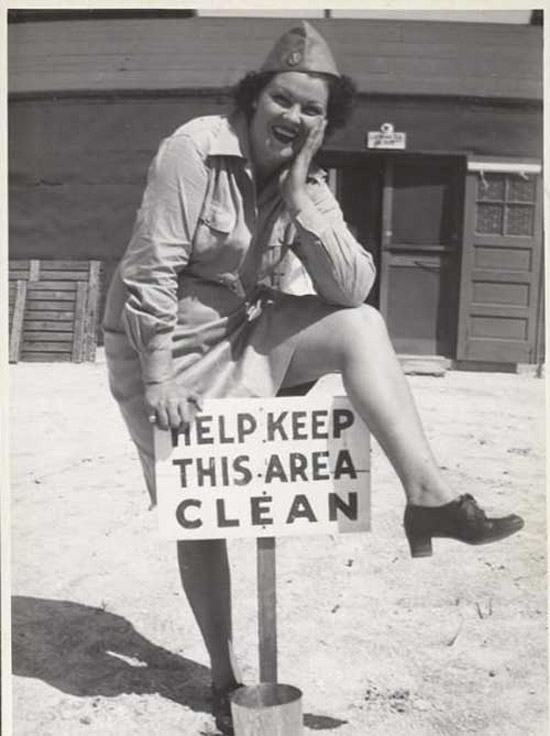 Vintage 1940s WW II Photo of woman i uniform spreading her leg over Help Keep This Area Clean sign