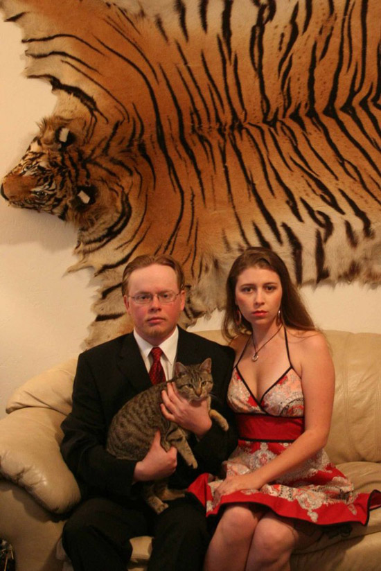 Funny Portrait: Strange couple with car in front of hanging tiger skin rug