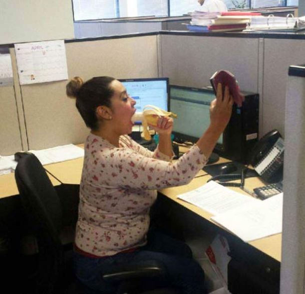 Woman at work taking a selfie of herself eating a banana