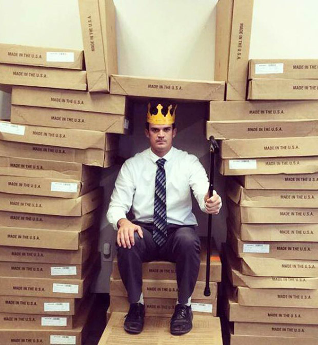 Man with crown sitting on thrown of boxes
