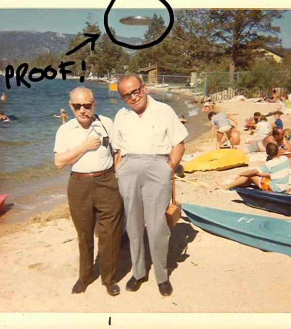 Vintage color snapshot of two old men on beach with ufo in background proof