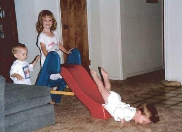 Awkward funny pic of kids on slide, young boy takes a face plant