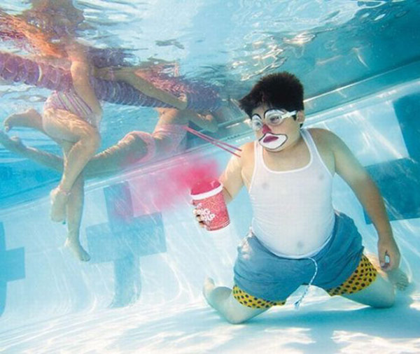 Funny photo of boy underwater in swimming pool in clown makeup holding a big gulp