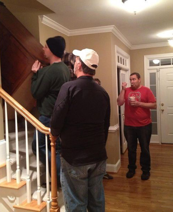 Funny pic of man eating ice cream watching movers move couch up stairs