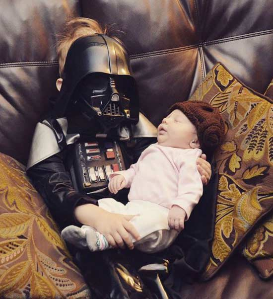 Funny Awkward Family Photos: boy dressed in Darth Vader costume holding a baby