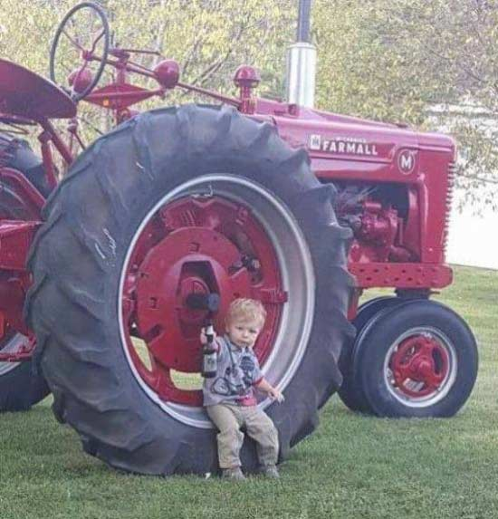 little boy sitting on tractor tire drinking beer