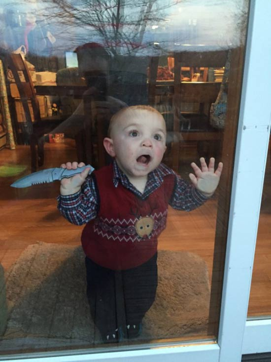 awkward baby with knife pressing face against sliding glass door