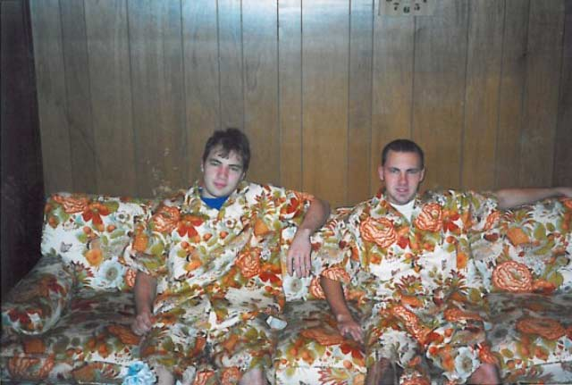 awkward brother in matching floral shirts & shorts sitting on couch with same pattern