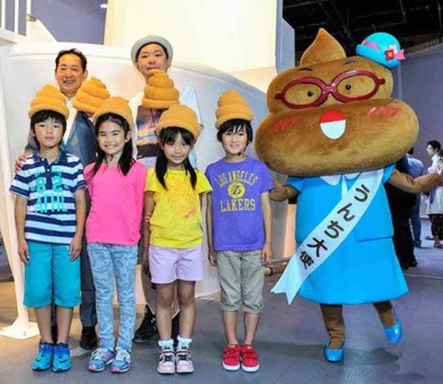 Japanese family at amusement park wearing poop hats posing with poop mascot