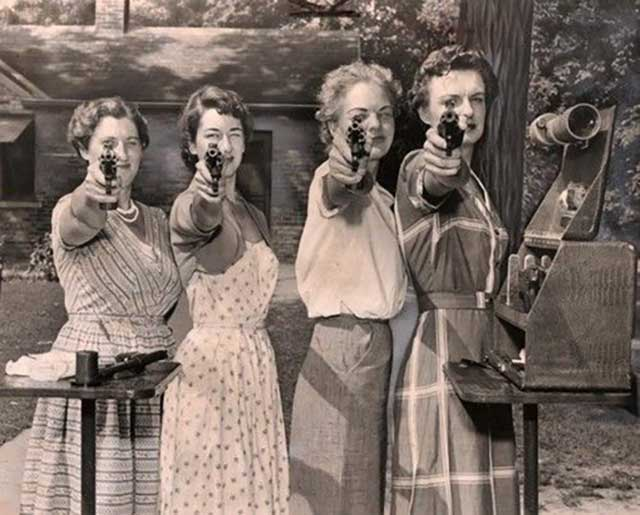 vintage old snap of woman with pistols at shooting range pointing them at camera