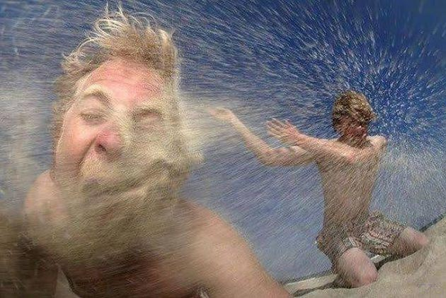 Funny pics~ crazy pop of sand thrown in face at the beach