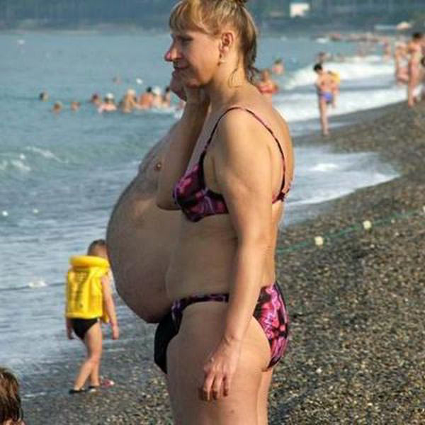 perfectly timed photos ~ woman on beach with fat man gut