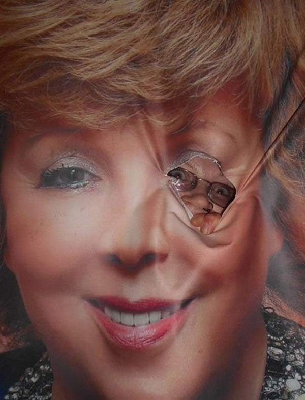 35 Funny Pics Memes ~ Creepy photo of man peeking through ripped sign of woman's eye