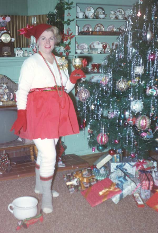 vintage snapshot of middle aged woman in elf outfit in front of Christmas tree