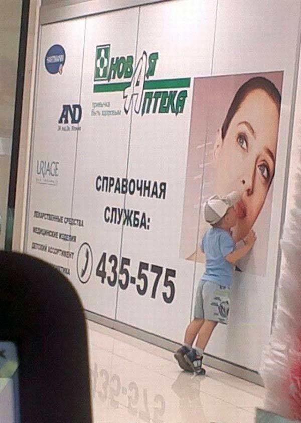 Funny photo of little boy kissing woman on wall ad