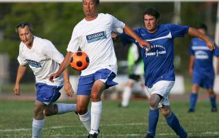 Fussball Challenge: Ältere Männer kämpfen um den Ball