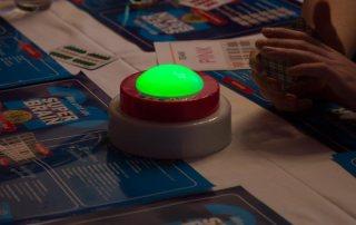 Quizshow grüner Buzzer auf Tisch