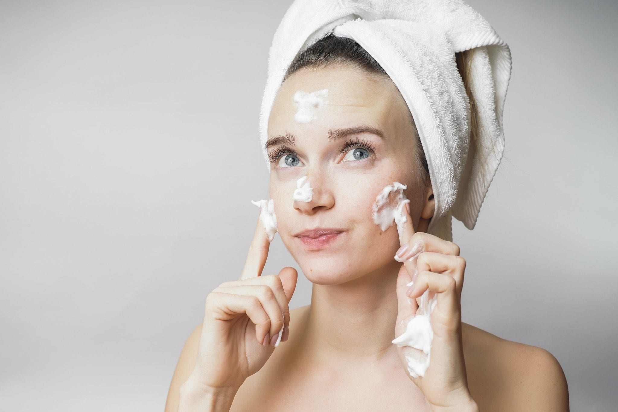 girl with cleanser on her face and hair wrapped in a towel
