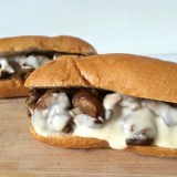 Grilled mushrooms and grilled onions with a light cheese sauce makes for the ultimate veggie cheesesteak. Recipe at Teaspoonofspice.com