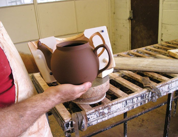 A slipcast Brown Betty is removed from its mold.