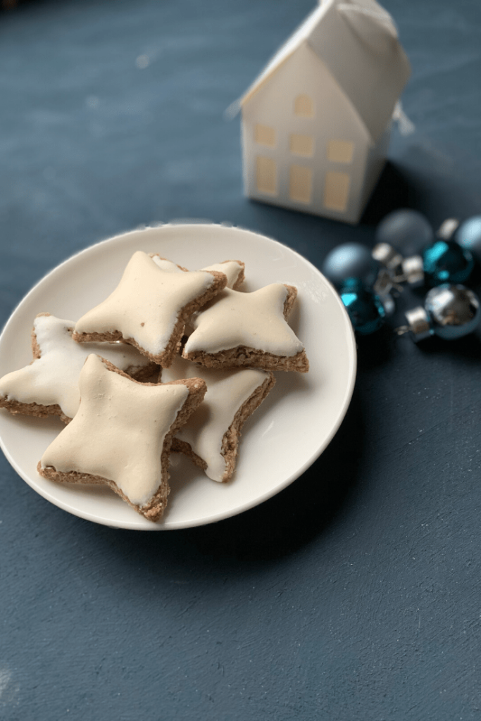 A plate of fresh German cinnamon stars - Zimtsterne - with Christmas decorations - traditional German Christmas baking - the aroma, taste, shape an look makes them the quintessential Christmas biscuit