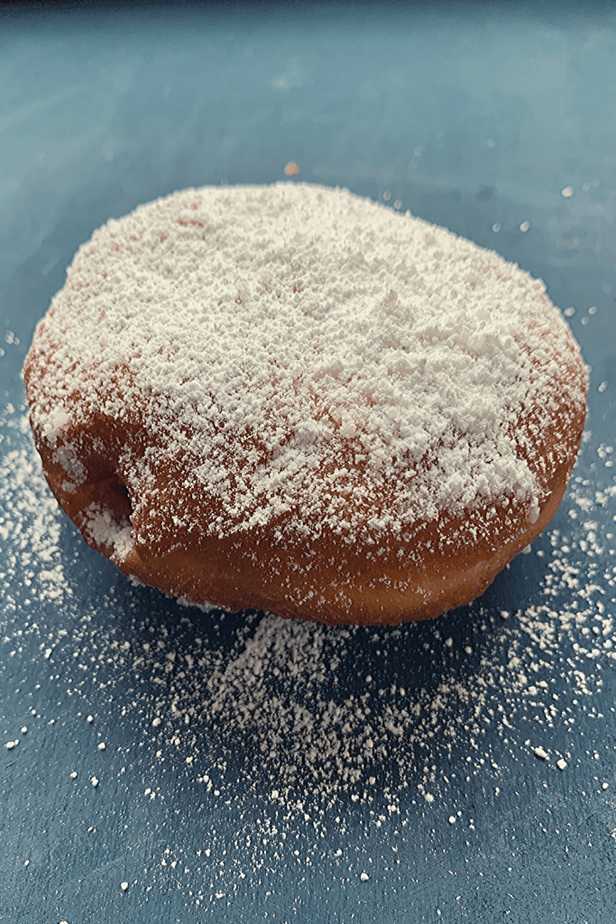 A fresh Berliner doughnut, dusted with icing sugar; traditional German recipe