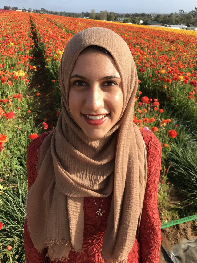 Nadah Fetieh looking happy surrounded by a field of red poppies
