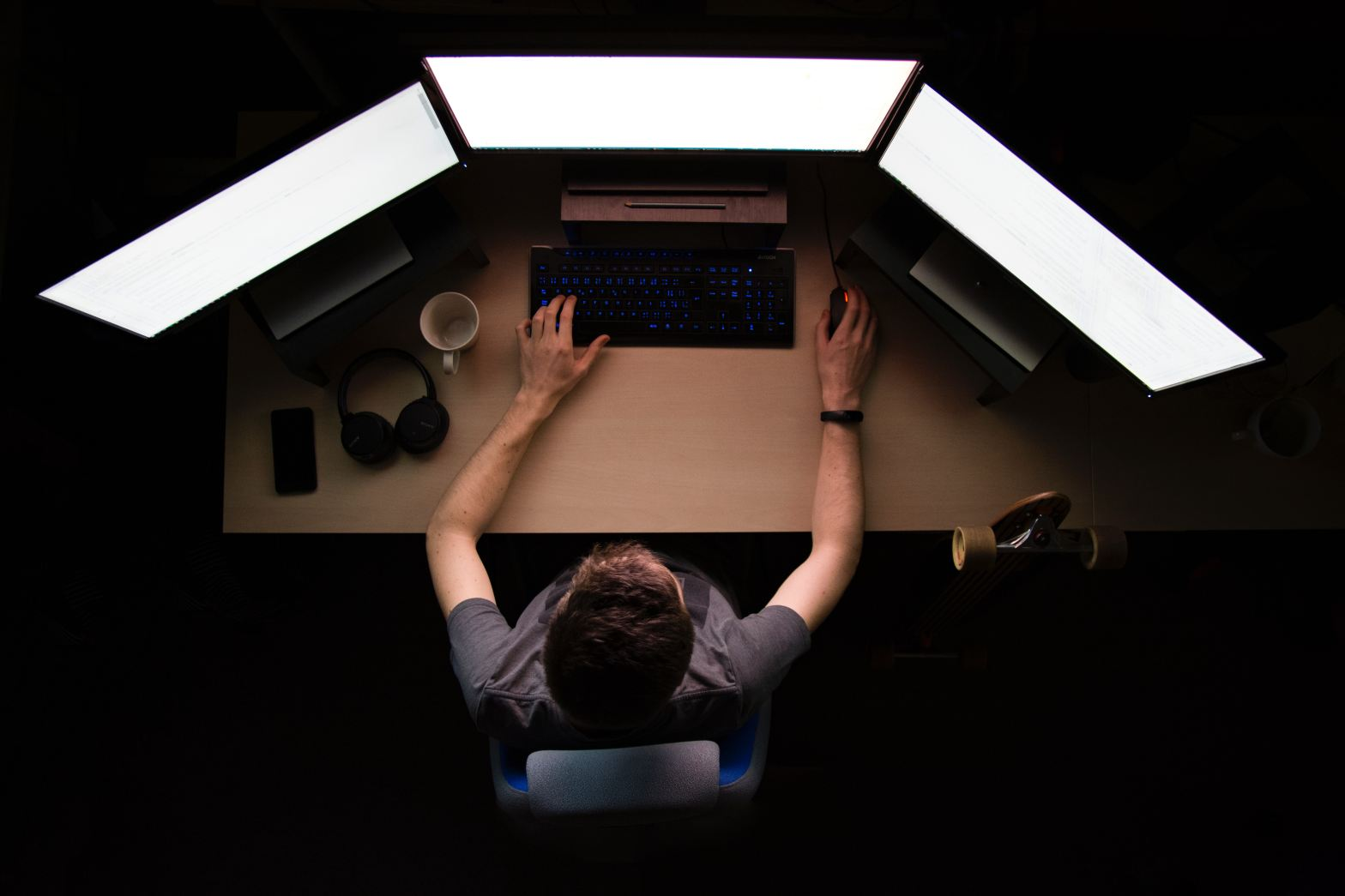 man facing three computer monitors while sitting