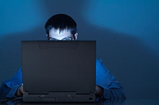 A man using a laptop works late into the night-778605