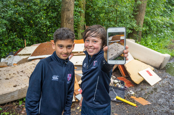 Two boys standing in front of a pile of rubbish