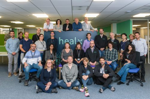 Group photo of the Healx team sitting and standing around a background of the company name