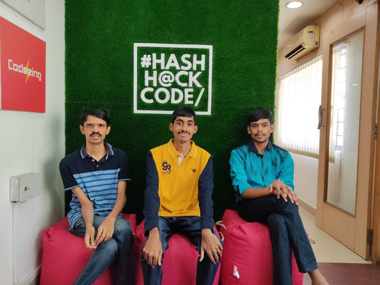 Three men sitting on a sofa in front of a wall with #HashHackCode